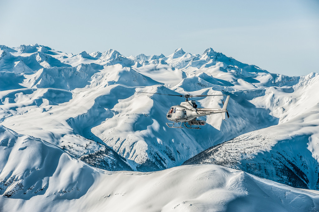 Helicopter Flying Heli Skiers in Remote Mountains in BC, Canada
